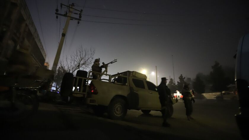 Afghan security forces take up positions near Kabul's Intercontinental Hotel, where a group of armed men staged an attack on Saturday.