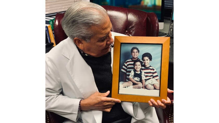Dr. Xavier Caro with a photo of his murdered children. From left is Joey, 11, Christopher, 5, and Michael, 8. He has a fourth son, who is now 20.