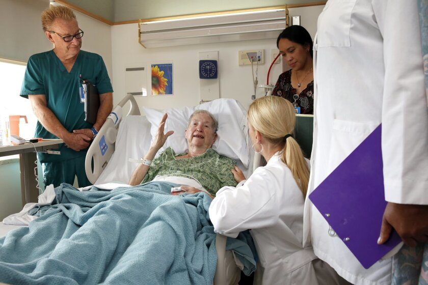 A navigator team meets with patient Mary Ellen Dillon of Chula Vista Friday, following a recent car accident. From left to right are nurse navigator Keith Fero, Dillon, Dr. Megan Hamreus (back to camera), and bedside nurse Cherie Burke. Also present is pharmacist Euphemia Uhegbu.