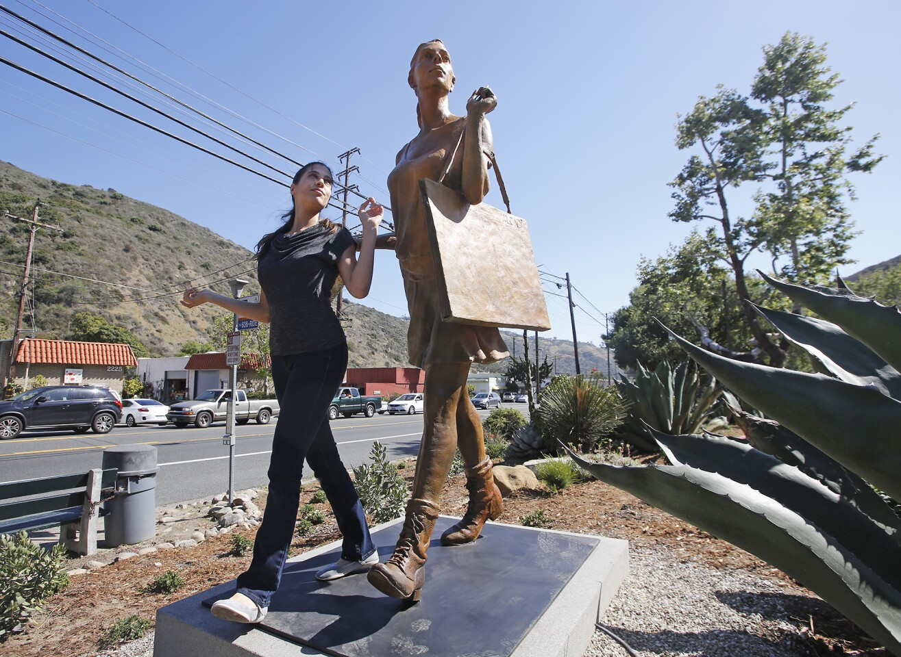 """Art model Ifat Glassman reenacts the pose she made for the sculpture """"The Art Student"""" during the Laguna College of Art + Design's unveiling ceremony Thursday for """"Canyon Walkers,"""" a trio of sculptures along Laguna Canyon Road in Laguna Beach."""