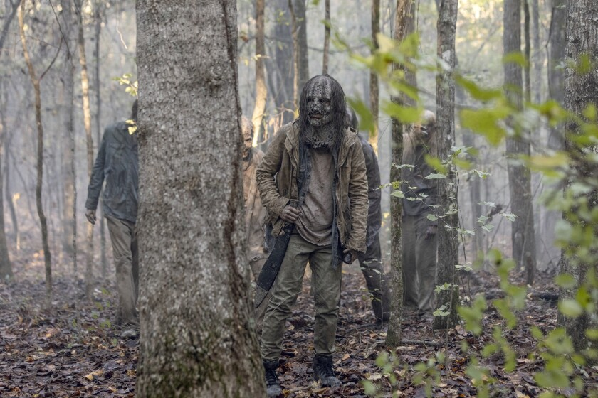 """The Whisperers wander in the woods in """"The Walking Dead."""""""