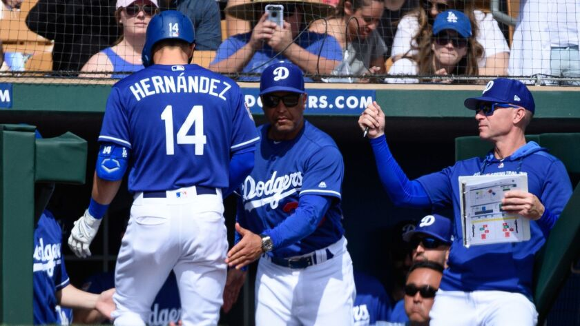 Dodgers manager Dave Roberts congratulates Enrique Hernandez, who hit a solo home run March 9 during a spring training game against Seattle.