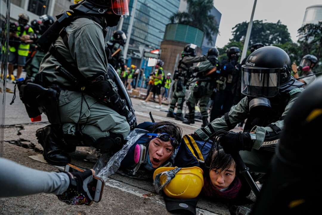 Police in riot gear pinned young protesters in Hong Kong.
