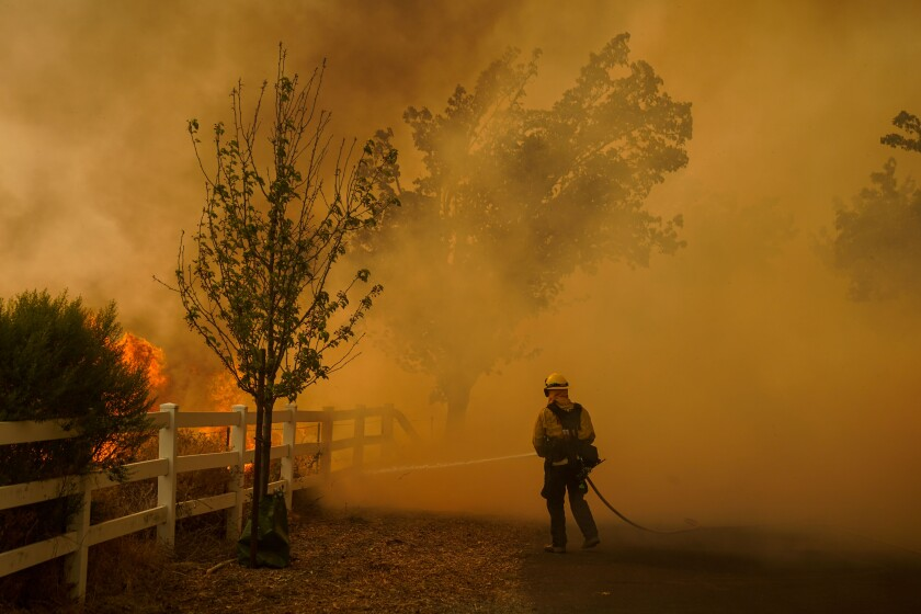 A firefighter wielding a hose fights the Hennessy Fire in Vacaville on Aug. 19.