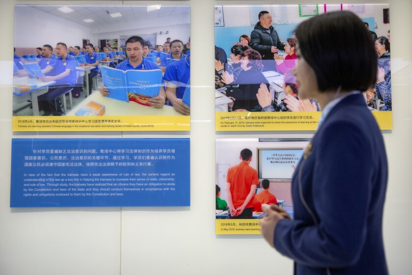 """A tour guide stands near a display showing images of people at locations described as vocational training centers in southern Xinjiang at the Exhibition of the Fight Against Terrorism and Extremism in Urumqi in western China's Xinjiang Uyghur Autonomous Region on April 21, 2021. Human rights groups and Western nations led by the United States, Britain and Germany accused China of massive crimes against the Uyghur minority and demanded unimpeded access for U.N. experts at a virtual meeting on Wednesday, May 12, 2021 denounced by China as """"politically motivated"""" and based on """"lies."""" (AP Photo/Mark Schiefelbein)"""
