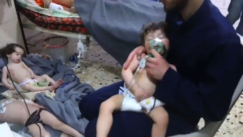 In an image taken from a video released by Syria Civil Defense, known as the White Helmets, a volunteer gives oxygen to a child at a hospital in Douma following a reported chemical attack on the rebel-held town on Sunday.