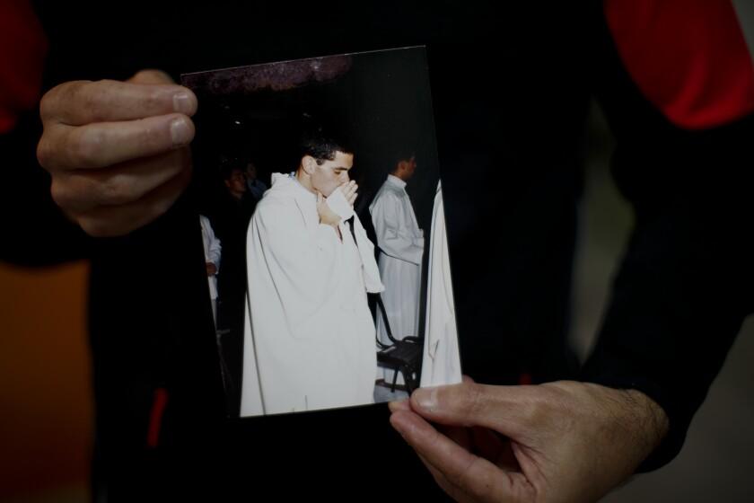 Andrés Gioeni muestra una fotografía de su ceremonia de ordenación para convertirse en sacerdote en 2000, luego de regresar a casa del obispado donde inició el proceso de apostasía en Buenos Aires, Argentina, el miércoles 17 de marzo de 2021. Gioeni, quien dejó el sacerdocio en 2021 y se casó con su novio en 2014, dijo que decidió abandonar formalmente la iglesia después de que el Vaticano decretó que la Iglesia católica no puede bendecir las uniones entre personas del mismo sexo ya que Dios 'no puede bendecir el pecado'. (AP Foto/Natacha Pisarenko)