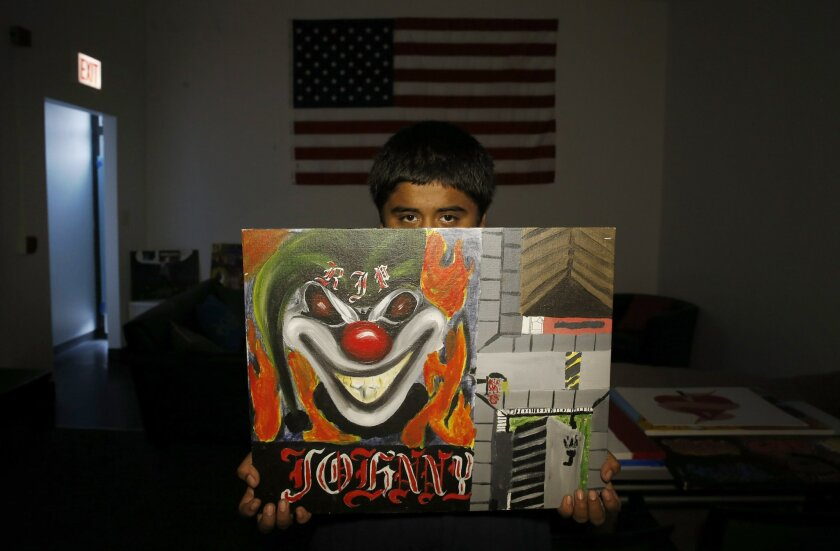 In this Aug. 27, 2014, photo, Fernando, 14, poses for a photo behind a painting he made to honor a dead friend Johnny in Chicago. When he was just 12, he witnessed a drive-shooting where one friend survived a bullet to the head and another died on Fernando's couch, awaiting an ambulance. Fernando i