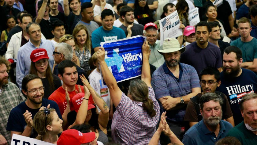 A woman holds up a sign for Hillary Clinton before being escorted out of a Donald Trump rally last month in San Jose.