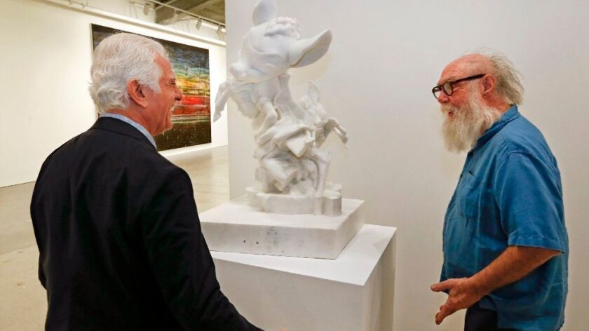 "Maurice Marciano and artist Paul McCarthy next to his piece ""White Snow and Bambi."""