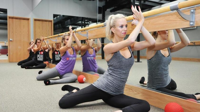 DiscoverSD reporter Michelle Dederko participates in barre class at Pure Barre as part of her I Dare You series. Taking the class with her are Pure Barre instructors (f-b) Hillary Hudson, Melissa Bermudez and Natalie Gerstner. (Rick Nocon / For The San Diego Union-Tribune)