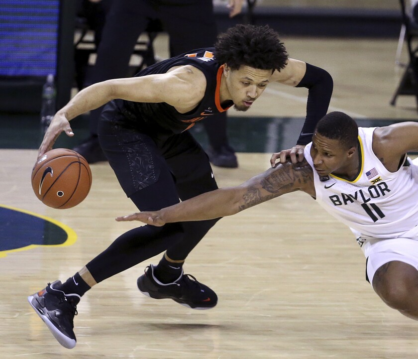 Baylor guard Mark Vital (11) tries to steal the ball from Oklahoma State guard Cade Cunningham (2) in the second half of an NCAA college basketball game, Thursday, March 4, 2021, in Waco, Texas. (AP Photo/Jerry Larson)