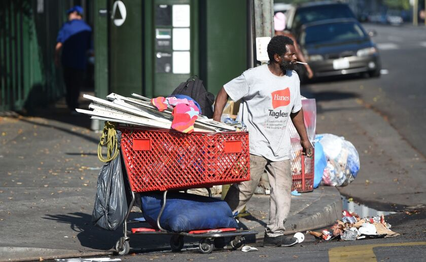A homeless man pushes his belongings in a shopping cart on skid row, which has one of the largest populations of homeless people in the United States.