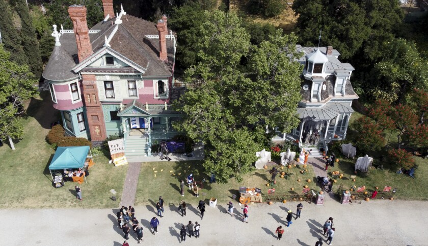 An aerial view of large Victorian houses with people in front.
