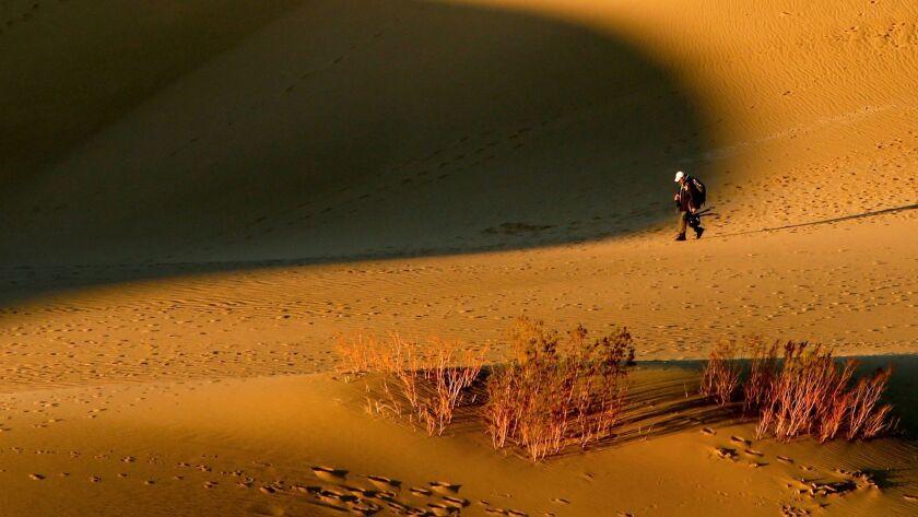 A lone hiker crosses Mesquite Flat Dunes, Death Valley National Park.