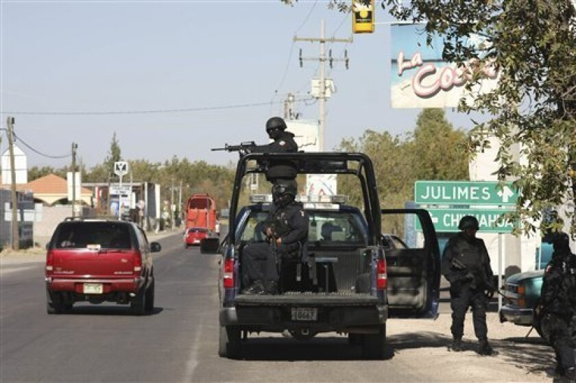 Mexican federal police officers man a roadblock in the town of Meoqui, state of Chihuahua, northern Mexico, Monday Nov. 29, 2010 after the police chief of  the town was gunned down. Authorities said gunmen on two trucks chased and killed the new female police chief, Hermila Garcia Quinones in a bor