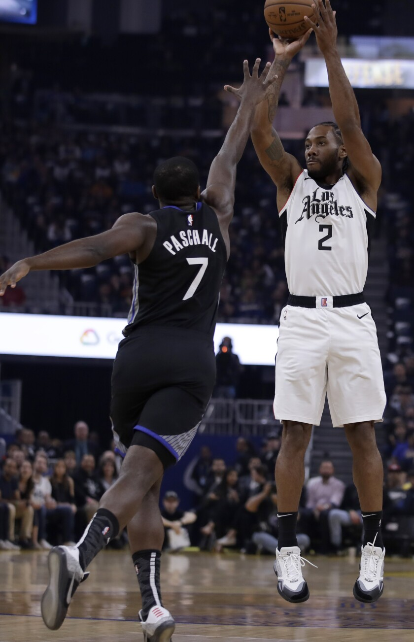 Los Angeles Clippers' Kawhi Leonard, right, shoots against Golden State Warriors' Eric Paschall (7) during the first half of an NBA basketball game Tuesday, March 10, 2020, in San Francisco. (AP Photo/Ben Margot)