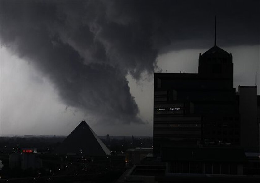 FILE - In this May 25, 2011 file picture, a line of severe storms crosses the Mississippi River in Memphis, Tenn., passing by the Memphis Pyramid. The dark formation was reported a few minutes earlier as a tornado in West Memphis, Ark. Nature is pummeling the United States in 2011 with extremes. There have been more than 700 U.S. disaster and weather deaths. What's happening, say experts, is mostly random chance or the bad luck of getting the wrong roll of the dice. However, there is something more to it, many of them say. Man-made global warming is loading the dice to increase our odds of getting the bad roll. (AP Photo/Lance Murphey, File)