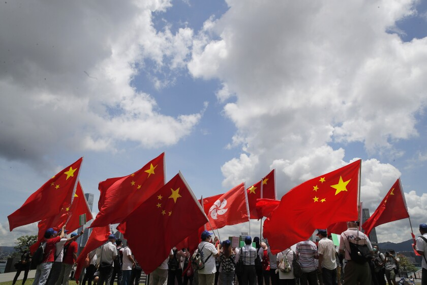 Pro-China supporters hold Chinese and Hong Kong national flags during a rally.