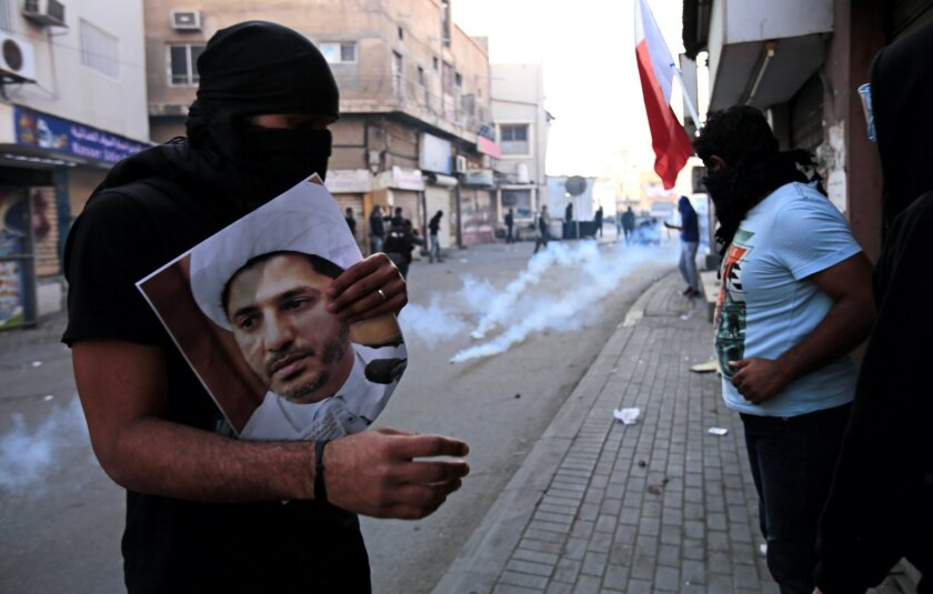 A masked Bahraini anti-government protester holds a picture of jailed Shiite cleric Sheik Ali Salman head of the opposition al-Wefaq political association, as riot police fire tear gas canisters during clashes in Bilad Al Qadeem, Bahrain, a suburb of Manama, Saturday, Jan. 3, 2015. Daily clashes be