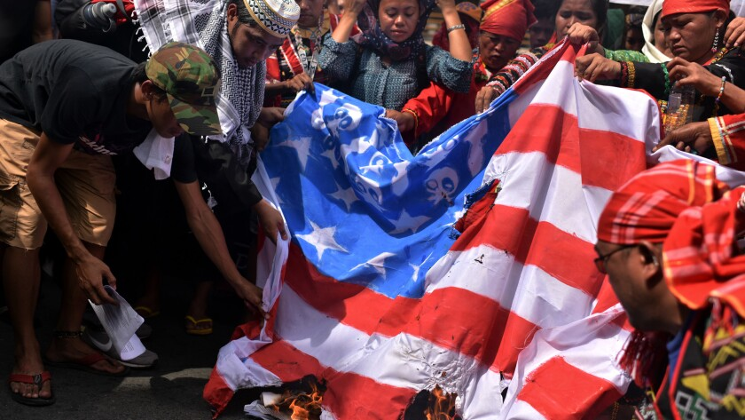 Members of an indigenous group and activists burn a U.S. flag during a protest Friday calling for the immediate pull-out of U.S. troops in the Philippines.