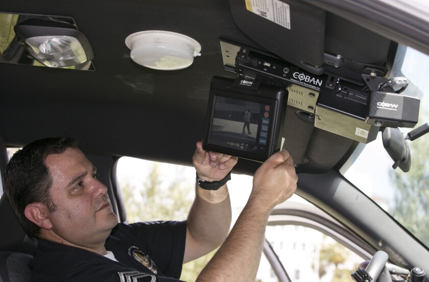 Los Angeles Police Sgt. Dan Gomez, a department expert on recording devices, shows a video display inside a patrol car with a camera pointed through the windshield at right, during a demonstration for media in Los Angeles in April 2014.