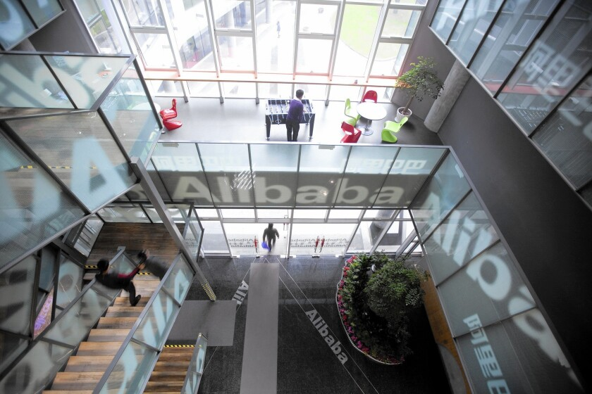 People walk through Alibaba's headquarters in Hangzhou, China. The e-commerce giant, which went public on Wall Street in September, has become a $263-billion juggernaut with far-flung interests in areas such as entertainment, mapping and banking.