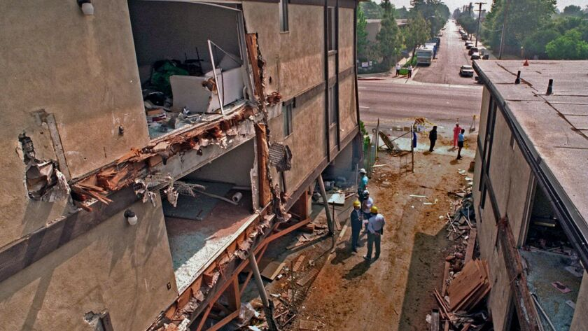 "Construction workers and investigators begin the slow task of ""controlled"" demolition at the remains of the earthquake-damaged Northridge Meadows apartment complex in 1994."