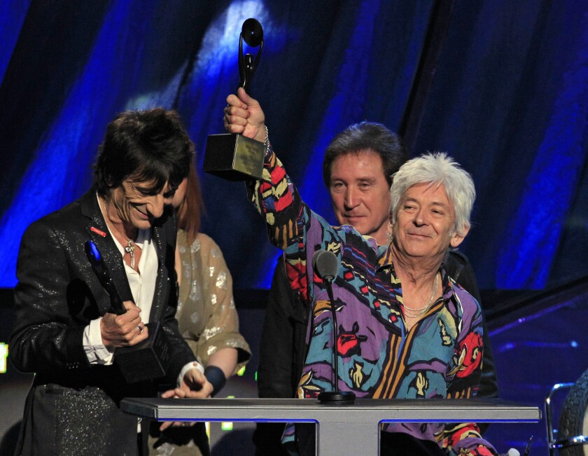 Ian McLagan, right, holds up his trophy in April 2012 after he and Ron Wood, left, and Kenney Jones, background, were inducted into the Rock and Roll Hall of Fame as members of the Small Faces/Faces, in Cleveland.