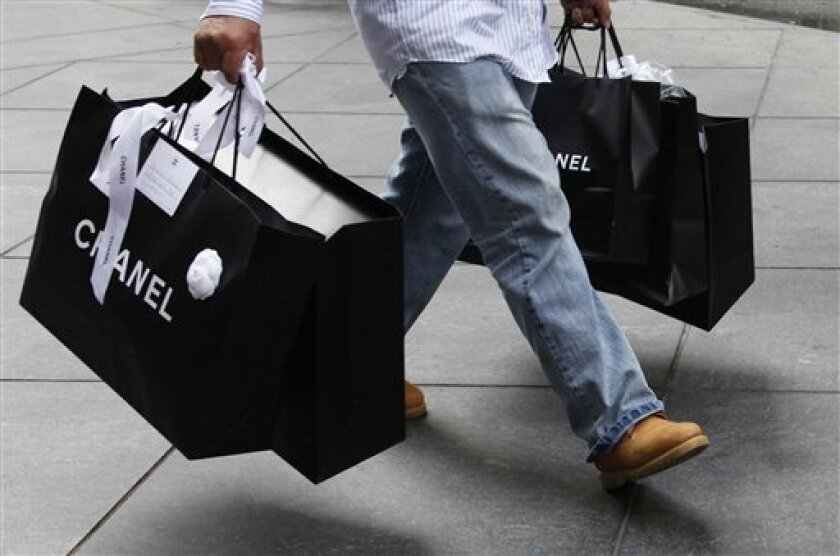 In this Oct. 25, 2010 photo, a man carries Chanel shopping bags, in New York. After a last-minute back-to-school buying spree, Americans appeared to have taken a shopping pause in October, resulting in a mixed retail sales picture.(AP Photo/Mark Lennihan)