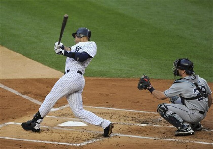 New York Yankees' Derek Jeter follows through on a double off Tampa Bay Rays starting pitcher Jeff Niemann in the first inning of a baseball game Thursday, July 7, 2011, at Yankee Stadium in New York. John Jaso caches for the Rays. (AP Photo/Kathy Kmonicek)