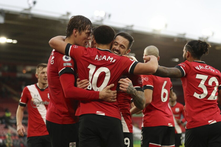 Southampton's Che Adams celebrates with his teammate Jannik Vestergaard, left and Danny Ings after scoring his side's opening goal during the English Premier League soccer match between Southampton and Sheffield United, at St. Mary's stadium in Southampton, England, Saturday, Dec. 13, 2020. (Naomi Baker/Pool via AP)