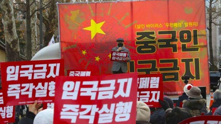Manifestantes surcoreanos durante una marcha para pedir que se prohíba la entrada de personas chinas en el país, cerca de la sede oficial de la presidencia, la Casa Azul, en Seúl, Corea del Sur.