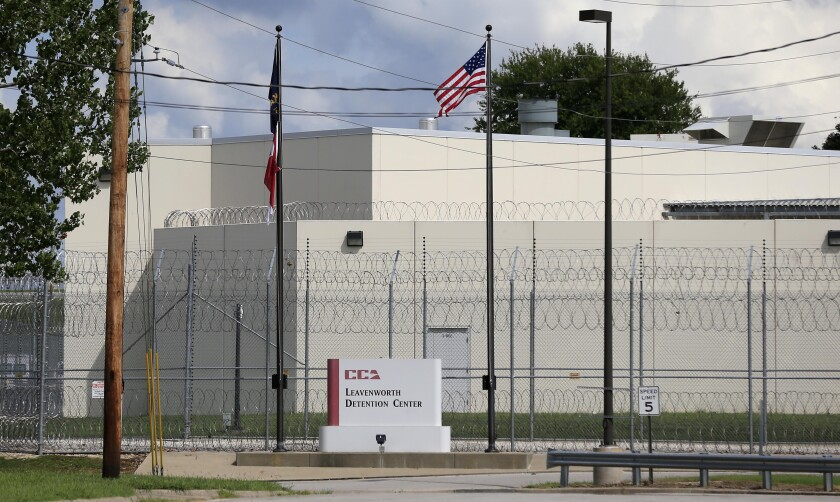 FILE - This Aug. 26, 2016, file photo shows a look down Highway Terrace in Leavenworth, Kan., at the main gate of the Leavenworth Detention Center of Corrections Corporation of America. The privately run maximum security federal prison in Kansas is dangerous and should be shut down when its contract expires at the end of this year, civil rights advocates and federal public defenders urged the White House in a letter Thursday, Sept. 2, 2021. (AP Photo/Orlin Wagner File)