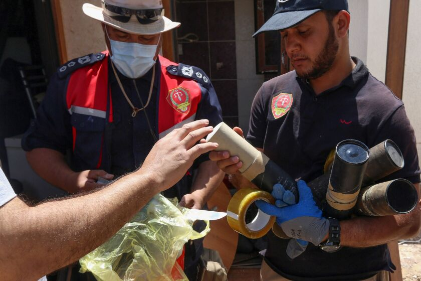Libyan deminers collect exploded mortar shells found in a suburb of Tripoli.