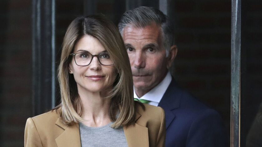 Actress Lori Loughlin and her husband, clothing designer Mossimo Giannulli, depart federal court in Boston in April.