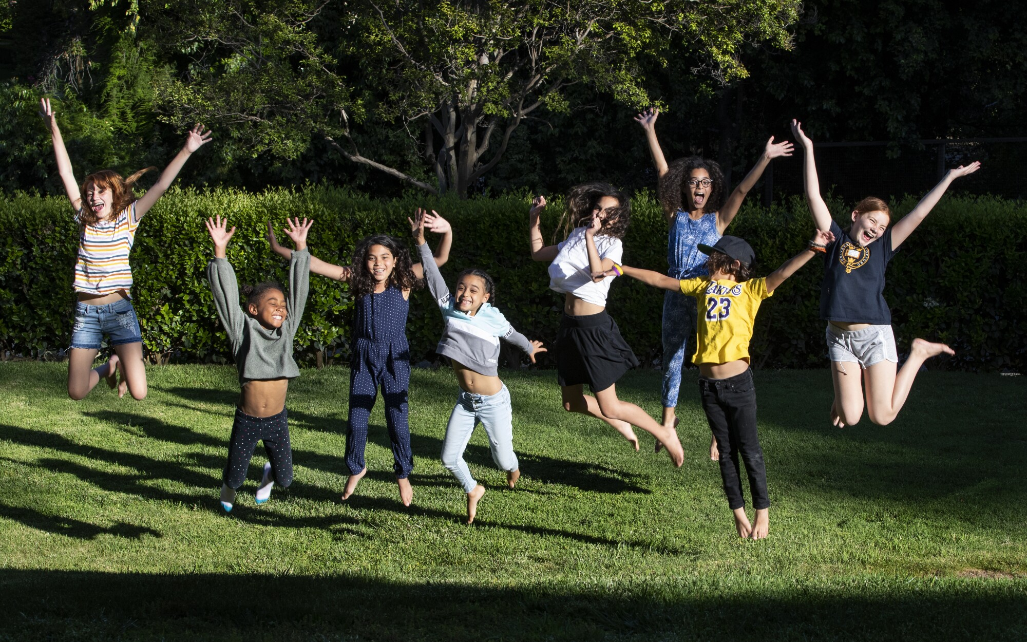 """The students of """"Brothbush Academy"""" cheer for their home school on the Roths' front lawn in Riverside."""