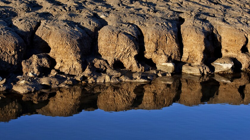 Patterns are created and reflected from water receding on the bed of Folsom Lake. As the state ends the fourth-driest water year on record with no guarantee of significant rain and snow this winter, Californians face the prospect of stricter rationing and meager irrigation deliveries.