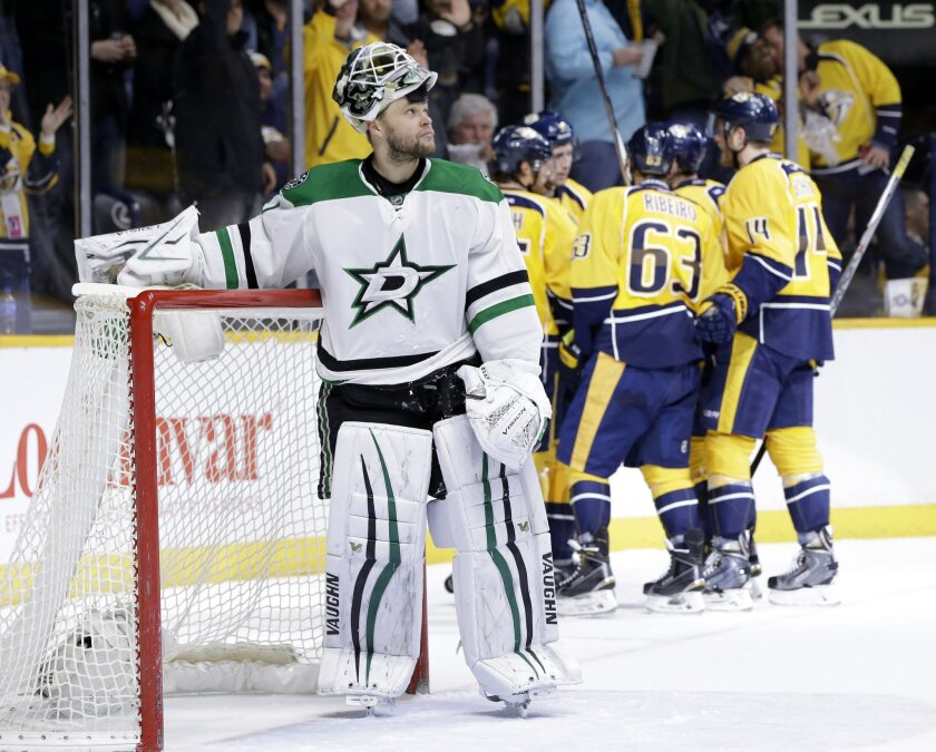 Dallas Stars goalie Antti Niemi, left, of Finland, watches the replay on the scoreboard as Nashville Predators players celebrate a goal by Filip Forsberg, of Sweden, in the second period of an NHL hockey game Monday, Feb. 15, 2016, in Nashville, Tenn. (AP Photo/Mark Humphrey)