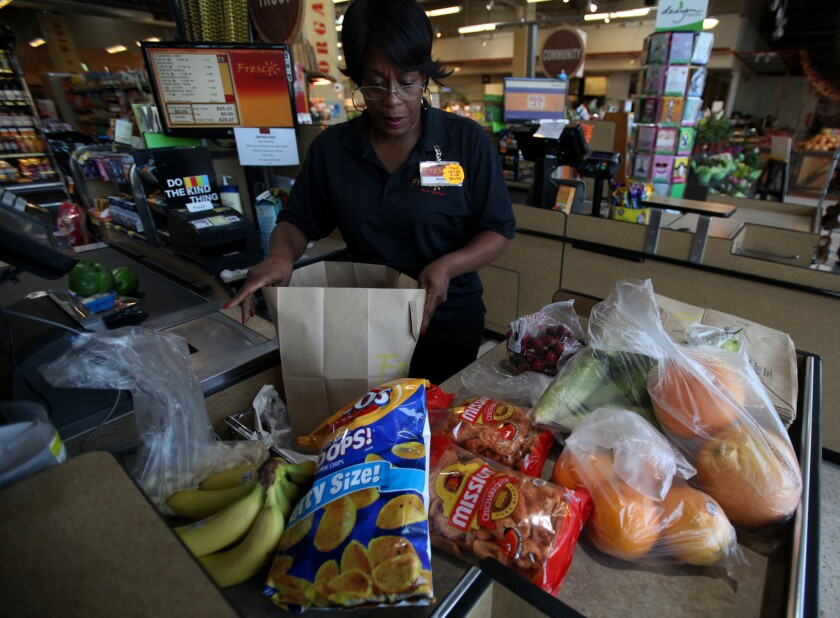 Cashier Sheila Curl puts groceries into a paper bag at Fresco Community Market in Los Angeles last year. Plastic carry-out bags are now banned in Los Angeles and a new bill would ban them statewide.