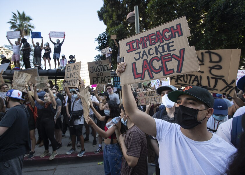 "Paul Villalobos holds a sign that reads ""Impeach Jackie Lacey"" on Spring Street in downtown Los Angeles"