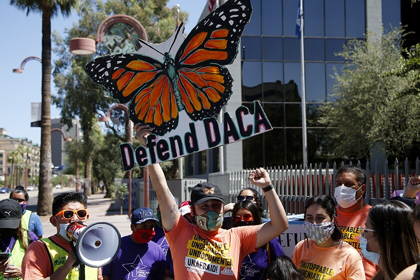 """People rally with signs and a megaphone. One large sign with a butterfly says """"Defend DACA"""""""
