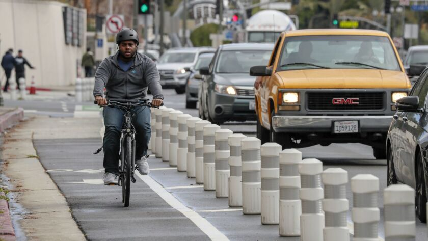 A bicyclist rides along Los Angeles Street near Temple where features have been added in an effort to reduce crashes. The mayor plans to spend $90.4 million on projects aimed at making the city less lethal for drivers, bicyclists and pedestrians.