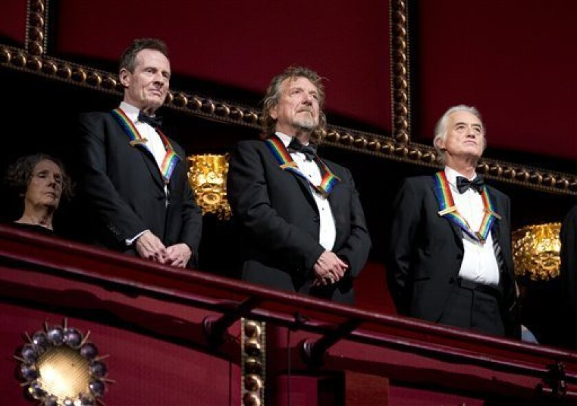 Rock band Led Zeppelin, from left, keyboardist/bassist John Paul Jones, singer Robert Plant, guitarist Jimmy Page, stand as the Star Spangled Banner is played during the Kennedy Center Honors Gala at the Kennedy Center in Washington, Sunday, Dec. 2, 2012. While Led Zeppelin is being honored as a ba