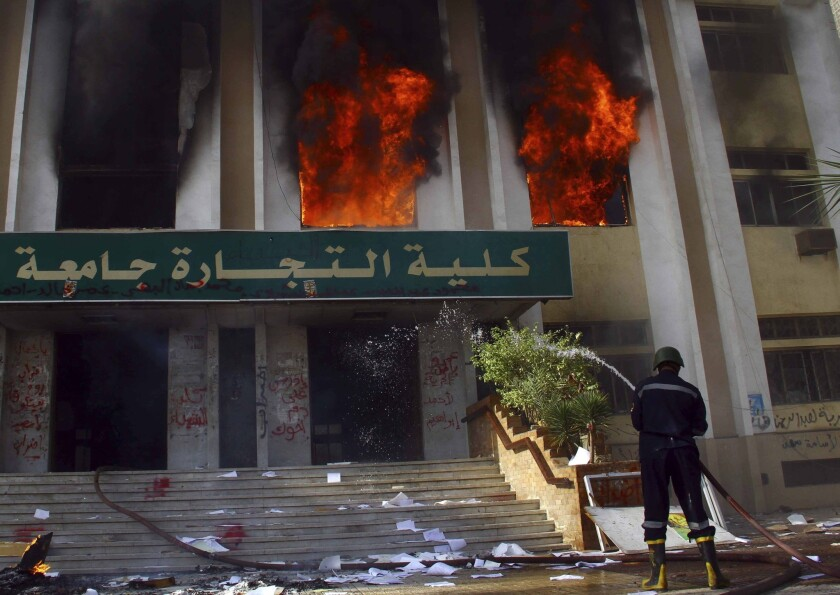 A firefighter tries to put out a blaze at an Al Azhar University building in Cairo, the site of clashes between government authorities and students who support ousted Islamist president Mohamed Morsi.