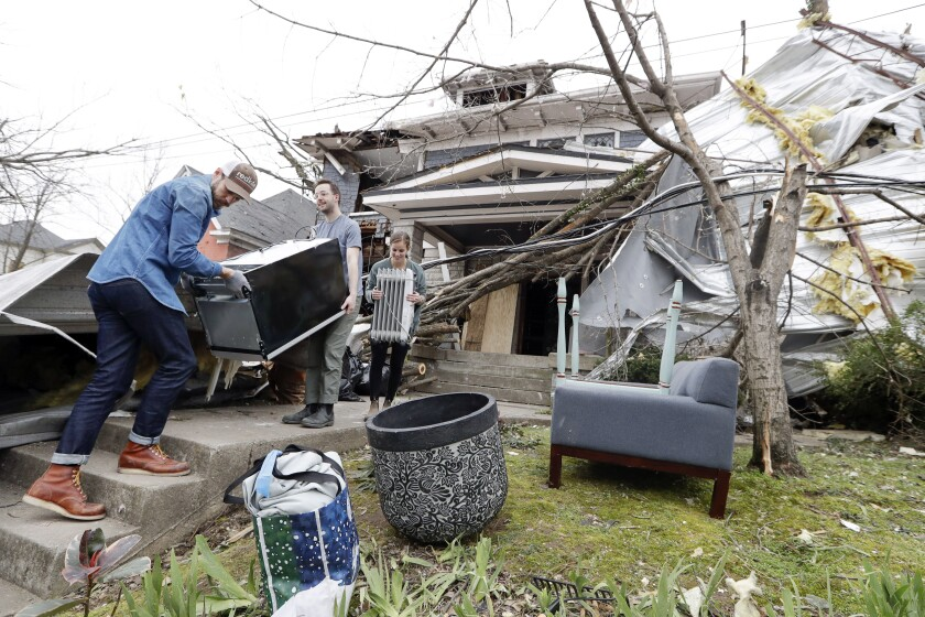 Benji Peck, left, and Austin Grove remove a refrigerator from a damaged home Wednesday, March 4, 2020, in Nashville, Tenn. Residents and businesses face a huge cleanup effort after tornadoes hit the state Tuesday. (AP Photo/Mark Humphrey)