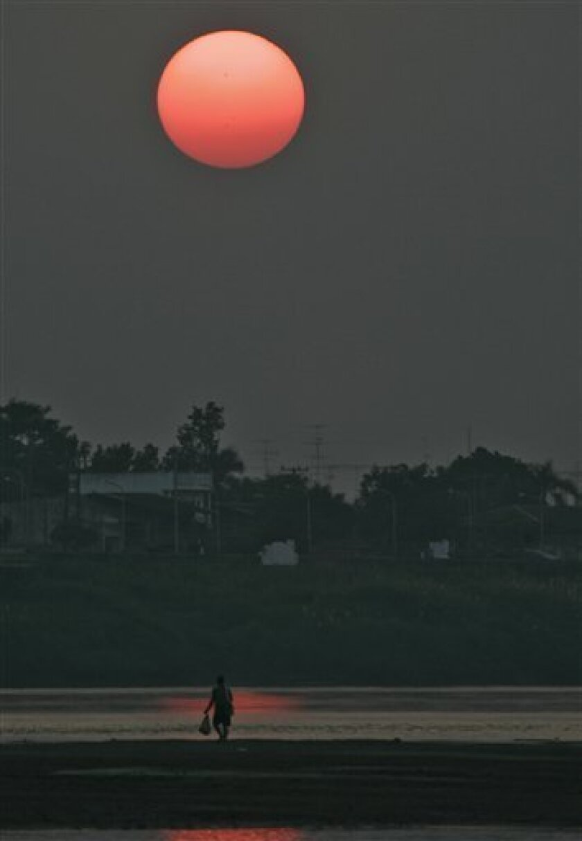 In this photo taken on Dec. 1, 2004, a man walks along the Mekong River at sunset near Vientiane, Laos. Plans for the first dam across the Mekong River anywhere in its meandering path through Myanmar, Laos, Thailand, Cambodia and Vietnam have set off a major environmental battle in Southeast Asia. The $3.5 billion Xayaburi dam project is slated for the wilds of northern Laos and aimed at generating power mostly for sale to Thailand. It pits villagers, activists and Vietnam against Thai interests and the Laotian government in its hopes of earning foreign exchange in one of the world's poorest countries. (AP Photo/David Longstreath)