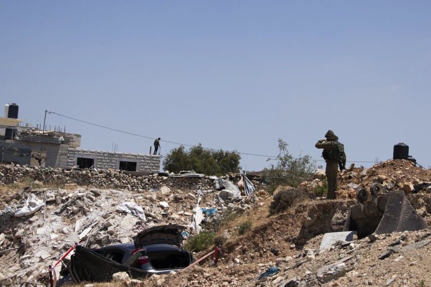 An Israeli soldier stands near a car said to be used in an attack near Hizmeh Junction in the West Bank, Wednesday, June 16, 2021. The Israeli military on Wednesday shot and killed a Palestinian woman who it said tried to ram her car into a group of soldiers guarding a West Bank construction site. (AP Photo/Maya Alleruzzo)