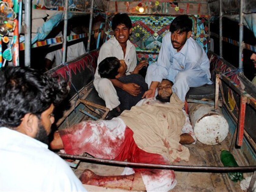 People bring injured men to a local hospital in Peshawar, Pakistan on Friday, Nov. 5, 2010. Three grenade blasts killed three people at a mosque in suburbs of Peshawar, where an anti-Taliban militia was active. (AP Photo/Mohammad Iqbal)