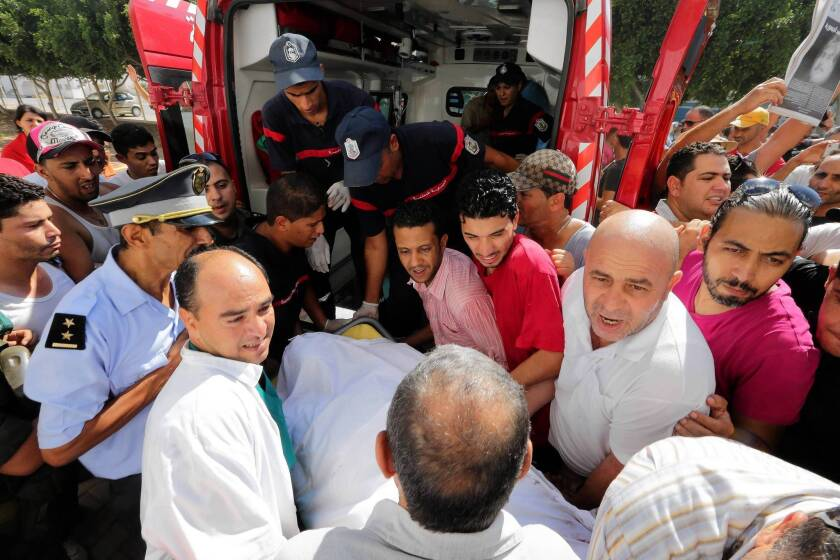 Medics carry away the body of slain opposition politician Mohammed Brahmi for an autopsy as protesters gather outside a hospital in Tunis, Tunisia.